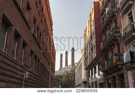 Barcelona-spain,september 29,2014: Street In Raval Quarter With Three Chimney At Background. Barcelo