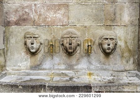 Barcelona. Three Ancient Stone Faces In Fountain.gothic Quarter.