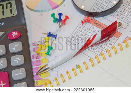 Analyzing Financial Data And Counting On Calculator. Graphics Calculator And Pen