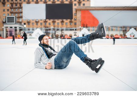 Young man in skates sitting on ice, skating rink