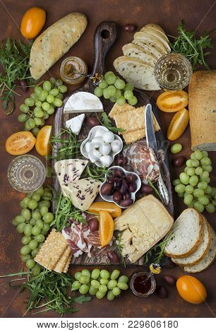 Different Appetizers On The Board Cheese, Prosciutto, Bread, Olives, Grapes And Wine