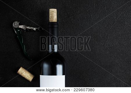 Bottle Of Wine With Corkscrew On The Black Stone Background  With Copyspace, Wine Degustation Concep