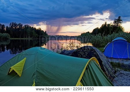 Summer Evening, A Small Camp On The Bank Of A Taiga River In Siberia. A Storm Is Approaching, A Clou