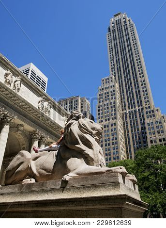 Little Girl On The Lion Statue At The Entrance To The New York Public Library