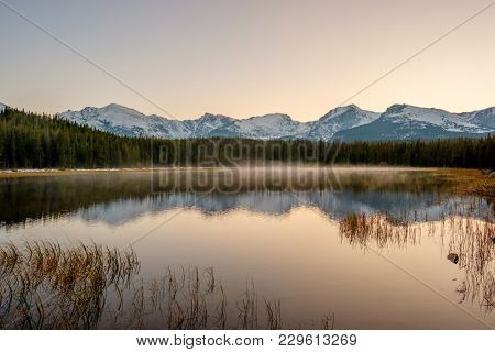 Bierstadt Lake and reflection with mountains in snow around at autumn. Fog on the water. Rocky Mountain National Park in Colorado, USA.