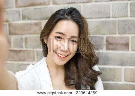 Asian Woman Using Smartphone With Smiling At Wall Background. Woman Using Smartphone For Selfie Or V