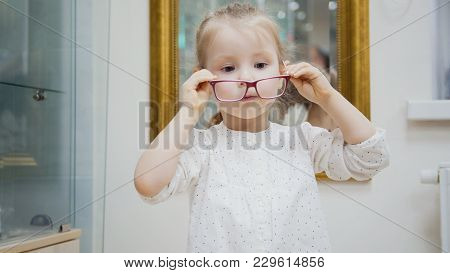 Little Girl Tries Fashion Medical Glasses Near Mirror - Shopping In Ophthalmology Clinic, Close Up
