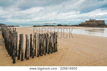 Wooden Poles On Beach During Low Tide And Fort National, 17-century Fortress On Island In Background