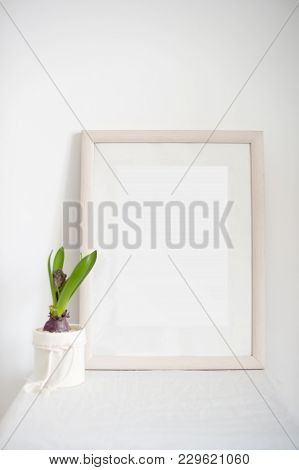 Laconic Frame On The Bedside Table In The White Interior