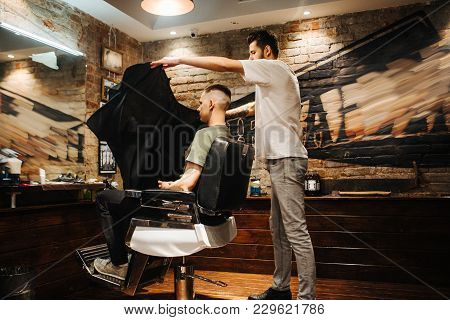 Making Hair Look Magical. Young Bearded Man Hairdresser At Barbershop. Soft Focus, Noise