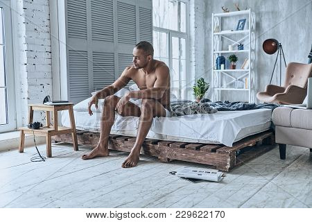 Just One More Minute In Bed. Sleepy Young African Man Trying To Wake Up While Sitting On The Bed At