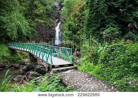 Bridge Over The Waterfall With Beautiful Waterfall Backdrop.