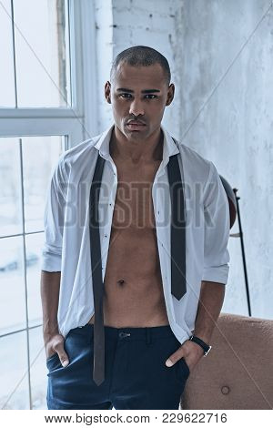 Real Man. Handsome Young African Man In Fully Unbuttoned White Shirt Looking At Camera While Standin