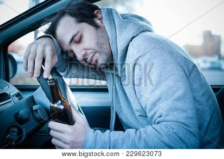 Young Man Driving His Car While Drinking Alcohol And Falling Asleep , Blue Effect Added To Increase