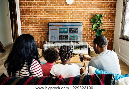 African family watching television together