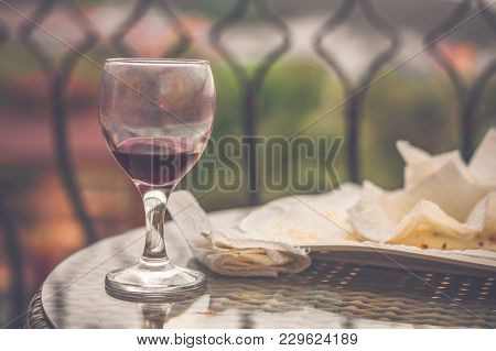 Red Wine In Dirty Wine Glass And Paper Napkins Left In Plate On Table