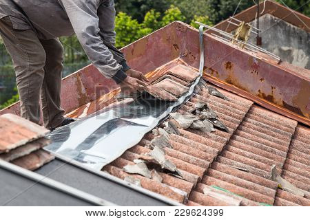 Asian Worker Replacing Roof Tiles Of Old Residential Building