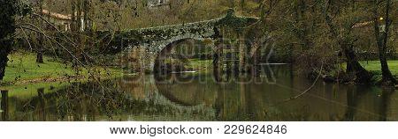 Roman Bridge Reflected On The River Arnoia, Allariz, Galicia. Spain