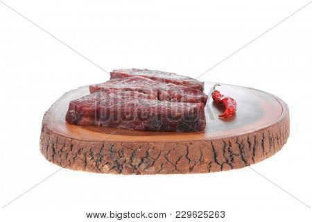 three fresh raw marble beef meat sirloin porterhouse steak on big wooden cutting plate with hot chili pepper isolated on white background