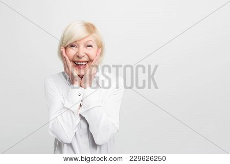 Old But Happy Woman Wears White Blouse And Showing That She Is Ery Surprised. She Has A Good Luck. I