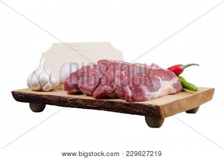 sirloin sinta fillet sliced on wooden plate with garlic and green red hot pepper isolated over white background with white empty menu plate for text near