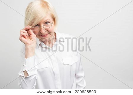 Cut View Of Mature Woman That Is Holding One Part Of Her Glasses And Looking Straight Forward. Somet