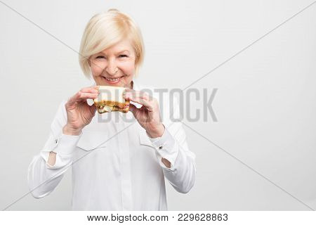 White-haired Woman Is Standing And Holding A Nice And Good Piece Of Sandwich. She Doesn't Have Time