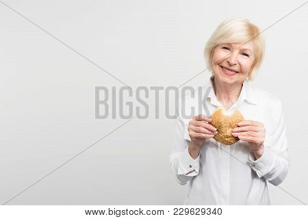 Old But Satisfied Woman Is Holding A Burger In Her Hands. She Has Just Made One Bite. This Lady Like