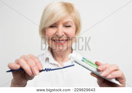 Close Up And Cut Vuew Of A Woman Putting Some Toothpaste On The Toothbrush. She Wants To Clean Her T