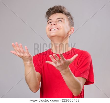 Happy Cute Child Reaching Out His Palms And Catching Something. Emotional Portrait Of Caucasian Teen