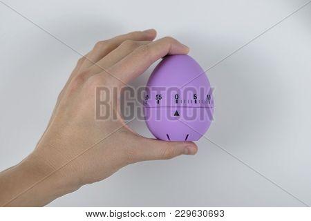 Hand Holding Violet Kitchen Timer Egg, Prepared For Decoration For Easter