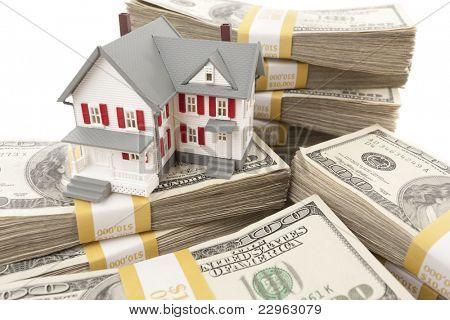 Pequena casa com pilhas de cem notas de dólar em branco.