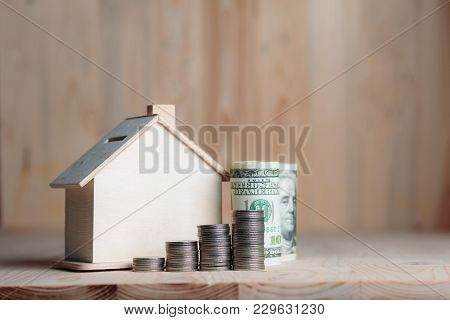 Wooden House Piggy Bank With Dollar Money And Coin On Wooden Table Over Wood Background Metaphor Sav