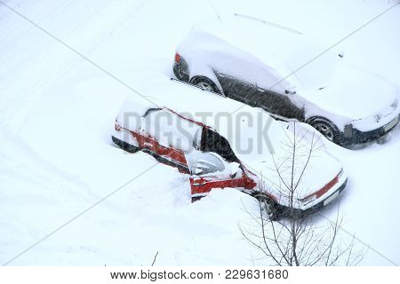 Man Trying To Free His Car From Snowy Captivity. Parked Cars Covered With Snow. Bad Weather In Town.