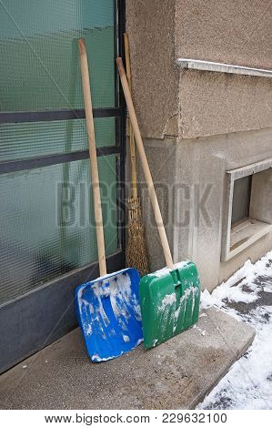 Two Snow Shovel Next To A Wall In Winter Time