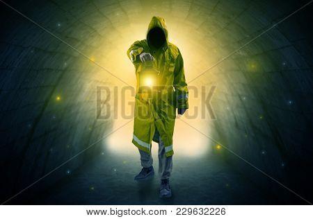 Ugly man in raincoat walking with glowing lantern in a dark tunnel