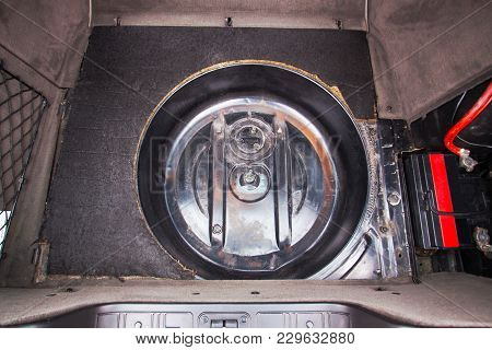 Place Under The Spare Tire In The Trunk Of The Car.
