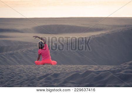 Woman Doing Yoga (sit) On Sand Dunes In Maspalomas.
