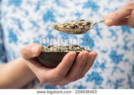 Close Up Of Woman Holding Bowl Of Mixed Seeds