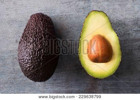 Overhead Shot Of Halved Avocado On Wooden Background