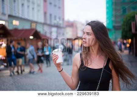 Girl With Long Hair Walk On Evening City Street, Travelling. Woman With Disposable Cup, Coffee Mood.