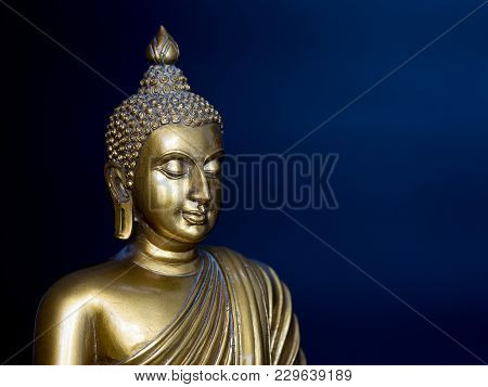 Golden Antique Buddha Statue. The Background Is Midnight Blue. The Face Of The Buddha Turned To The