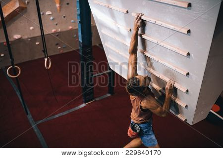 Female Instructor Giving Instructions To A Man On Wall Climbing. Man Learning The Art Of Rock Climbi