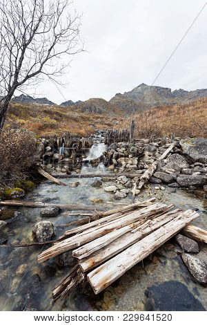 A Stream That Was Dammed For Gold Mining. The Dam Is Falling Apart. Mountains Are Seen In The Backgr