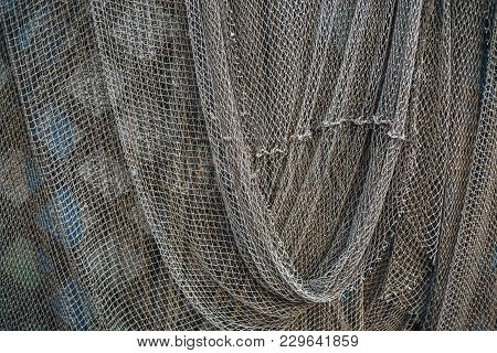 Dark Green Fishing Nets Weigh On The Fence. Abstract Background