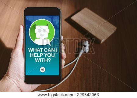User Hand Holding Mobile Chatting With Chat Bot On Phone Screen At Blur Wood Table,share Video On So