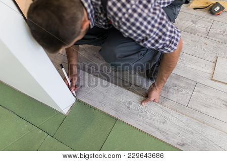 Male Worker Installing Laminate Flooring, Man Installing New Wooden Laminate Flooring. Man Laying La