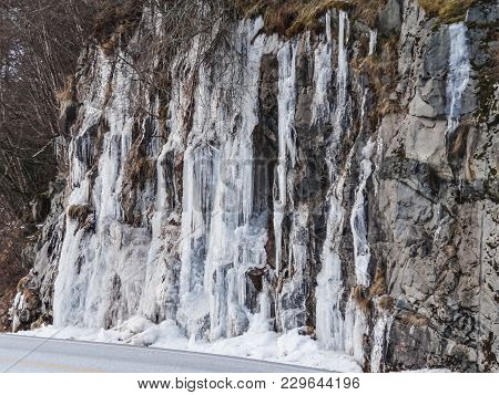 Frozen Waterfall Plunging From A Steep Rock Cliff Beside The Road