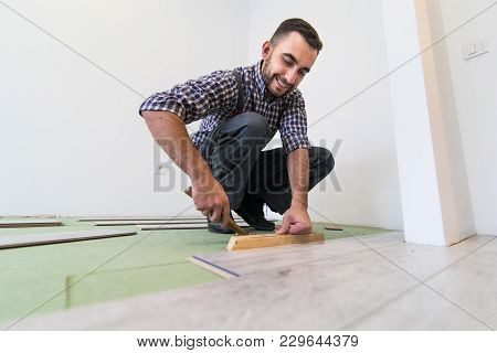 Repair Man Making The Laminate Flooring Installation