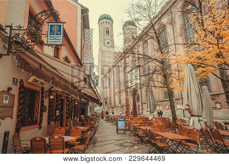 Munich, Germany - November 16, 2017: Street With Tables Of Beer Bar And 15th Century Frauenkirche Ch